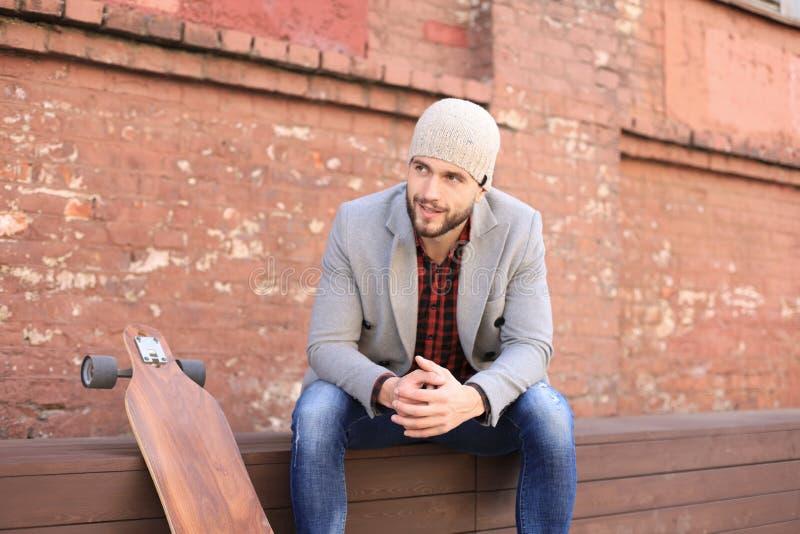 Przystojny młody człowiek siedzi w popielatym żakiecie i kapeluszu z longboard, odpoczywający, Miastowy jeździć na deskorolce poj zdjęcia stock