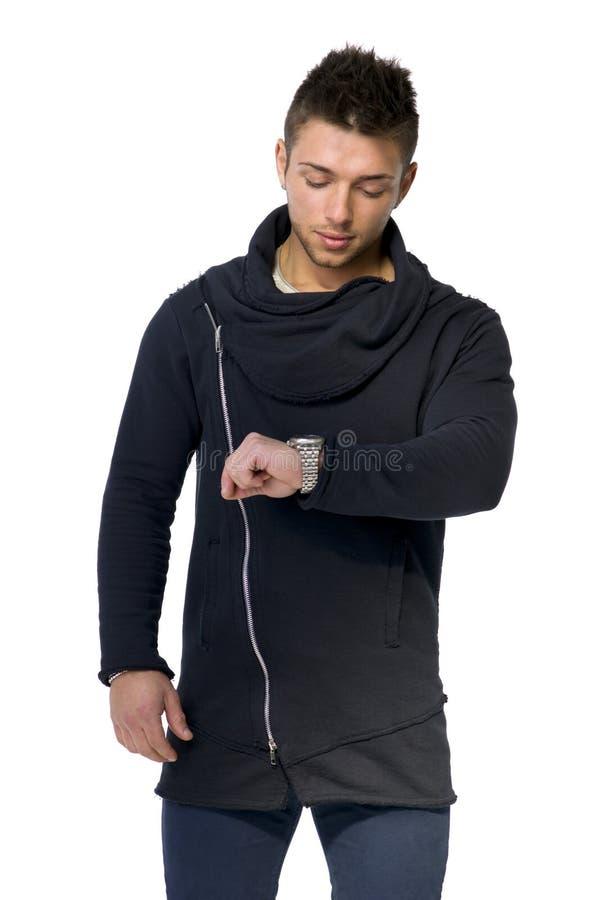 Przystojny młody człowiek sprawdza zegarek na jego nadgarstku fotografia royalty free