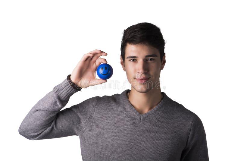 Przystojny młody człowiek trzyma małą piłkę z smiley twarzą na nim obraz stock