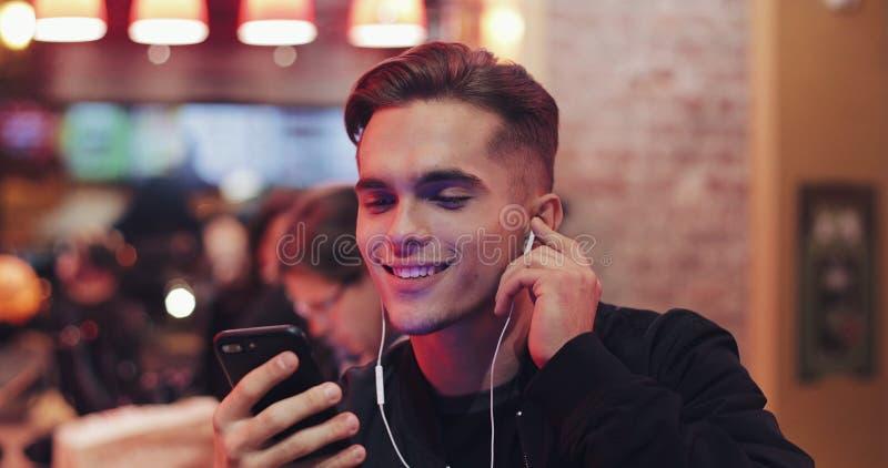 Przystojny młody człowiek używa hełmofony i jego smartphone dla wideo wezwania Siedzi przy barem blisko neonowych znaków rozochoc fotografia royalty free