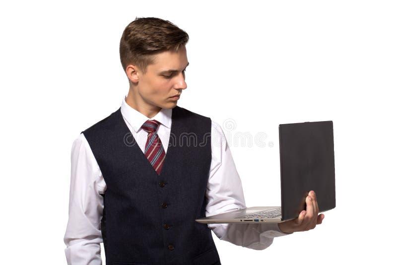 Przystojny młody człowiek używa jego laptop i patrzejący je stoi przeciw białemu tłu zdjęcie royalty free