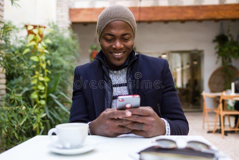 Przystojny młody człowiek używa jego telefon komórkowego w kawiarni fotografia stock