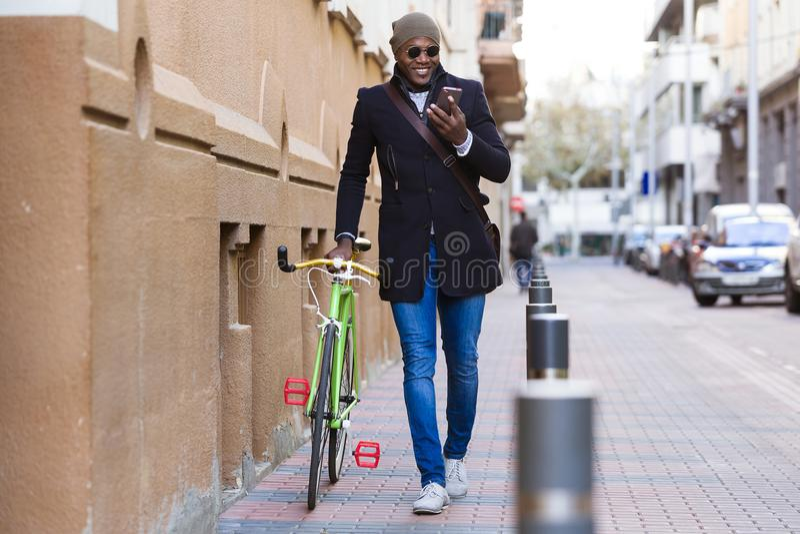 Przystojny młody człowiek używa telefon komórkowego i załatwiającego przekładnia bicykl w ulicie obraz royalty free