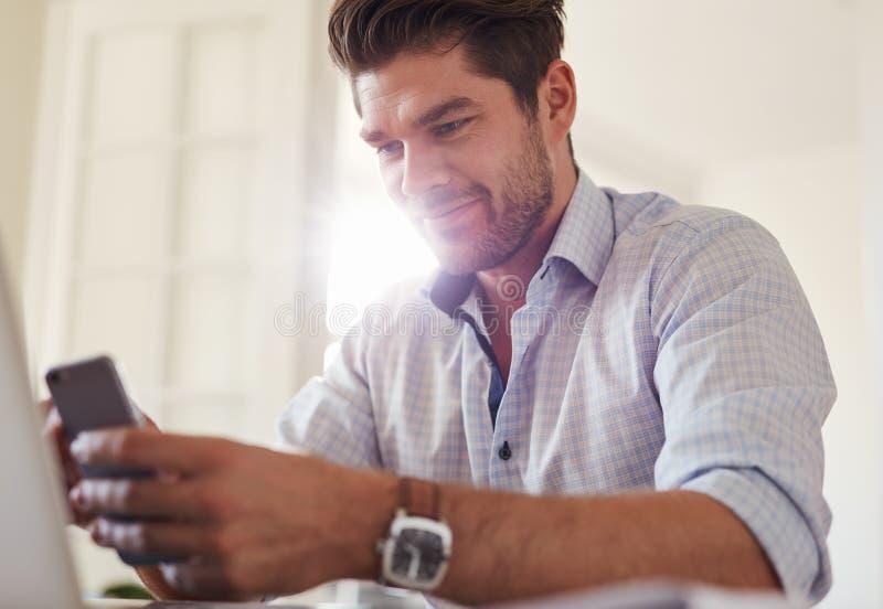 Przystojny młody człowiek używa telefon komórkowego w domu fotografia royalty free