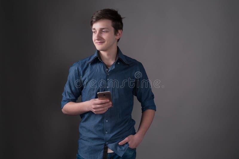 Przystojny młody człowiek w błękitnym koszulowym mienia smartphone, patrzeć daleko od i zdjęcie royalty free