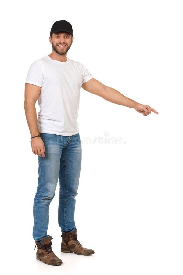 Przystojny młody człowiek W cajgach, Białej koszulce I Czarnej nakrętce, Jest Przyglądającym kamerą I Wskazywać W dół obraz royalty free