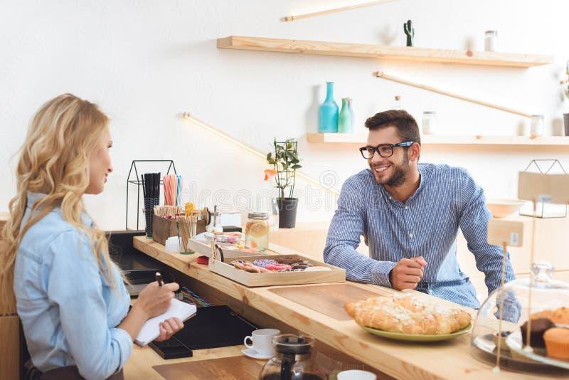 przystojny młody człowiek w eyeglasses uśmiechniętych i patrzeją kelnerki bierze notatki obrazy royalty free