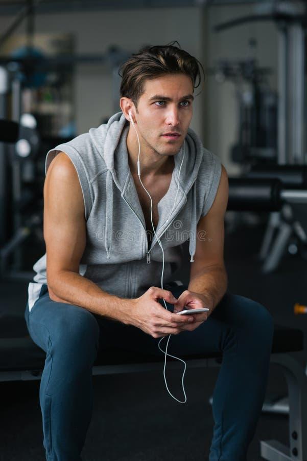 Przystojny młody człowiek w hełmofonach używać jego mądrze telefon przy gym zdjęcie royalty free