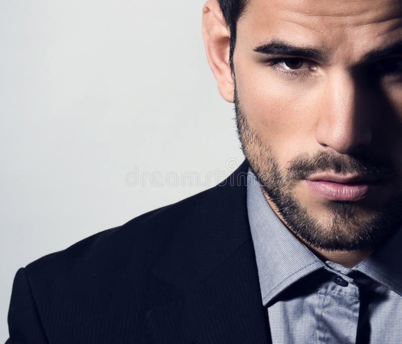 Przystojny młody człowiek w kostiumu na popielatym tle obrazy stock