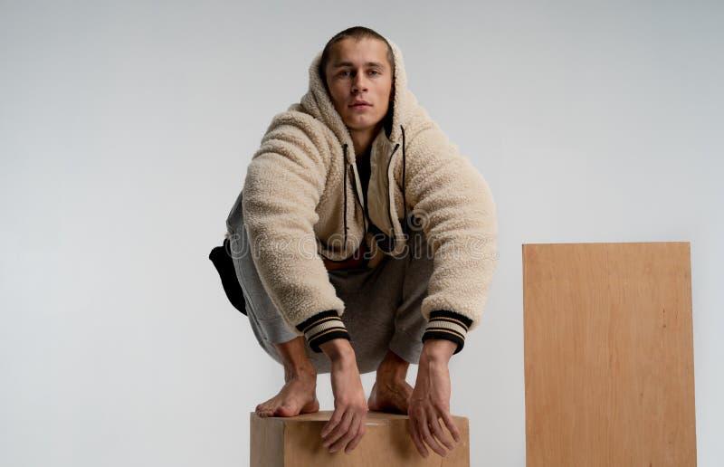 Przystojny m?ody cz?owiek w modnym sportswear obsiadaniu na drewnianym sze?cianie w czlowiek-paj?k pozie, patrzeje kamer? odizolo zdjęcie stock
