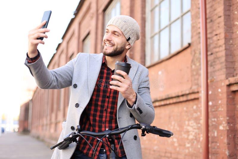 Przystojny młody człowiek w popielatej żakieta i kapeluszu chodzącej pozycji ulicy pić kawowy i brać selfie zdjęcie stock