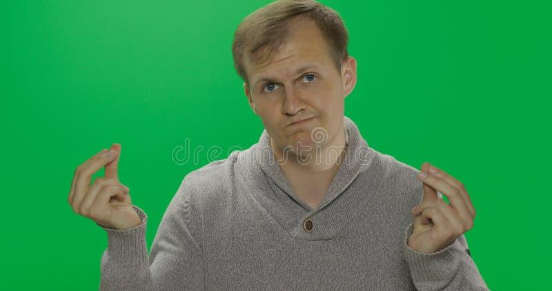 Przystojny młody człowiek w pulowerze robi żadny pieniądze gestowi ub?stwo Chroma klucz zdjęcie stock