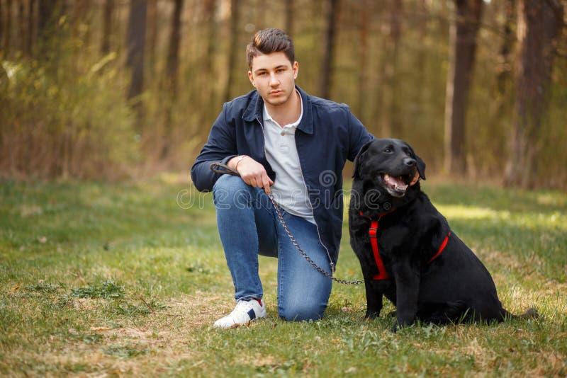 Przystojny młody człowiek z czarnym labradora psa odprowadzeniem w parku zdjęcia stock