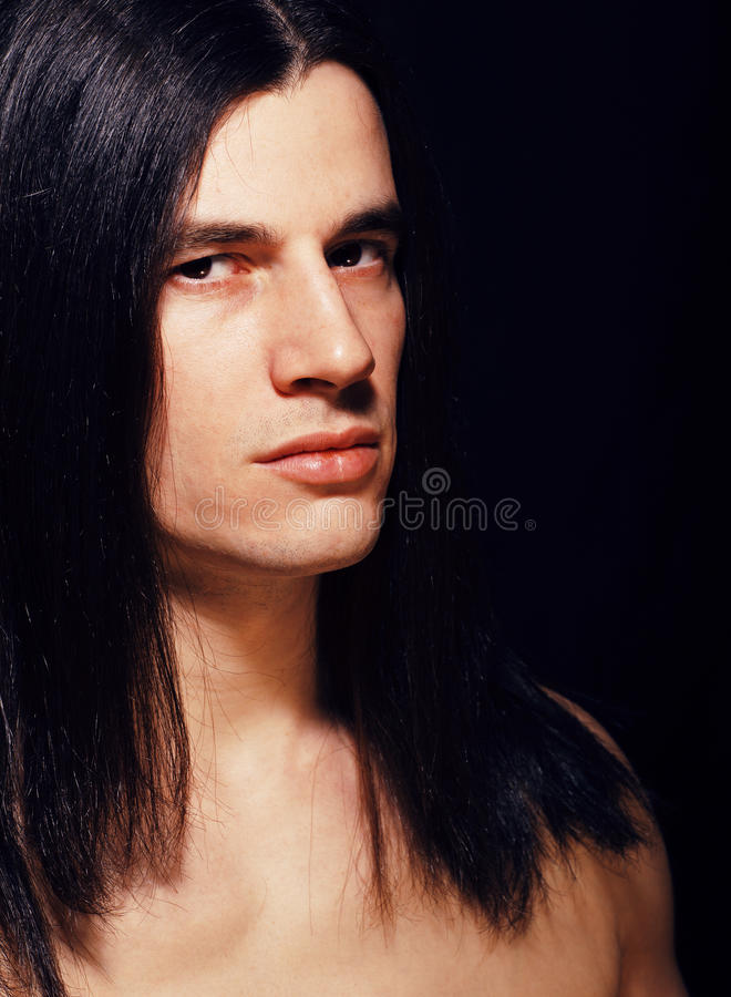Przystojny młody człowiek z długie włosy nagą półpostacią na czarnym backgroun obraz royalty free