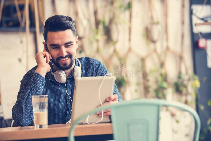 Przystojny młody człowiek z hełmofonami używać pastylkę w sklep z kawą fotografia stock