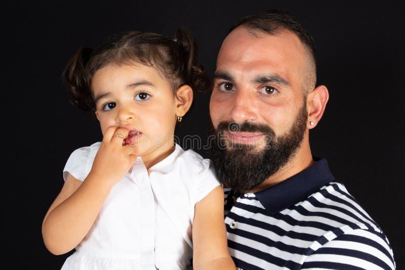 Przystojny młody człowiek z jego małą śliczną dziewczyną w Szczęśliwym dzień ojca na czarnym tle zdjęcie stock