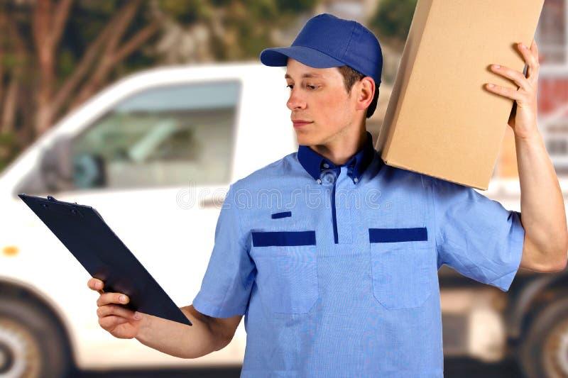 Przystojny młody doręczeniowego mężczyzna przewożenia kartonu pudełko obrazy royalty free