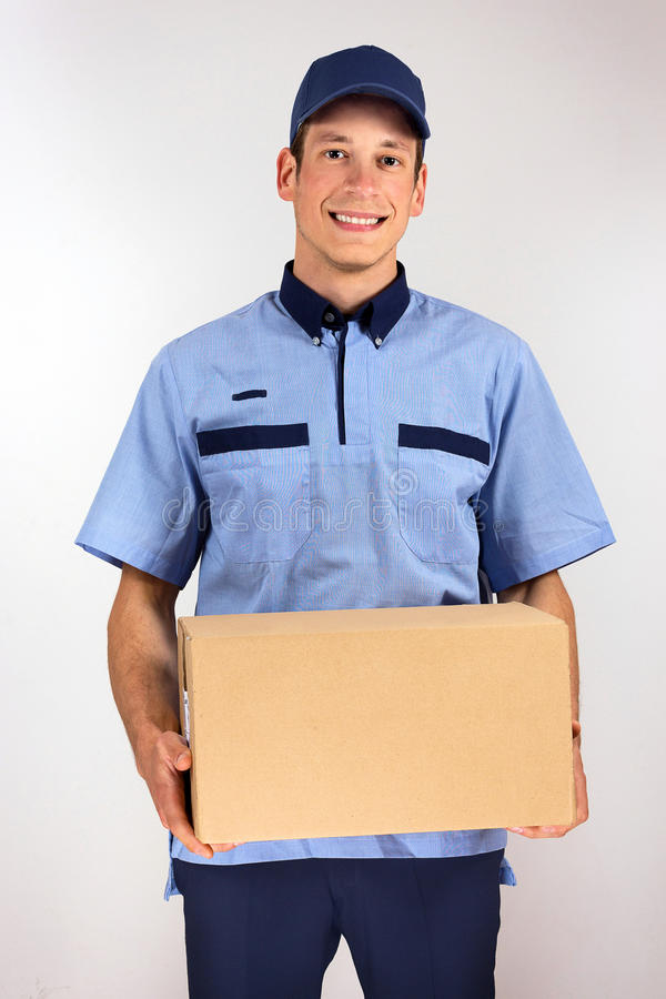Przystojny młody doręczeniowego mężczyzna przewożenia kartonu pudełko fotografia stock