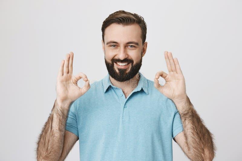 Przystojny młody dorosły z brodą i błyszczący uśmiech, pokazywać zadowalającego gest lub approvement z dwa rękami nad szarość, zdjęcia royalty free