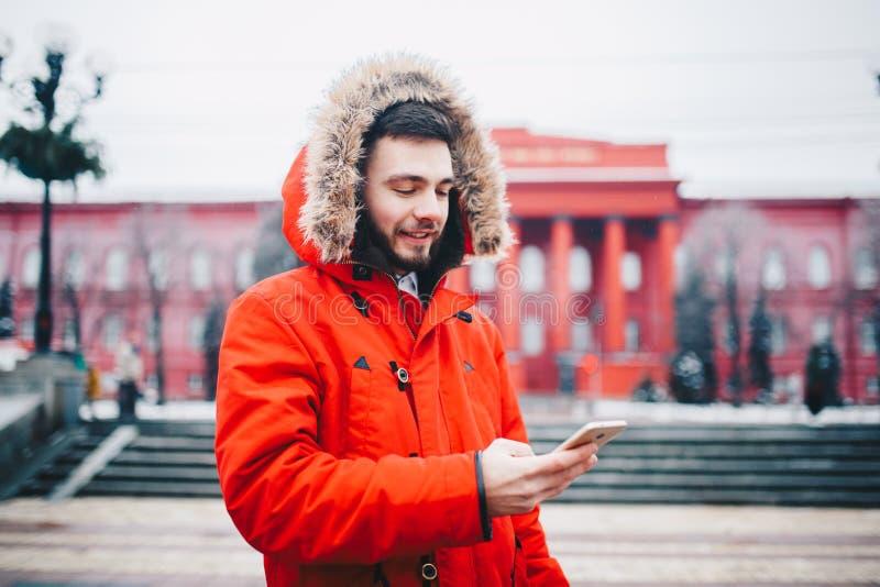 Przystojny młody facet z brodą i czerwieni kurtka wewnątrz okapturzamy ucznia uses telefon komórkowy, piszemy, piszemy, korespond obrazy royalty free