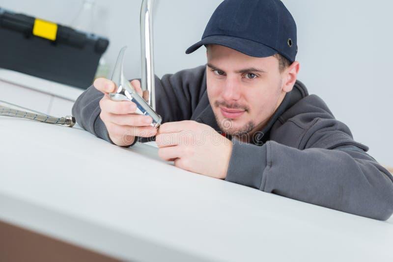 Przystojny młody hydraulika naprawiania klepnięcie przy cleints stwarza ognisko domowe zdjęcie royalty free