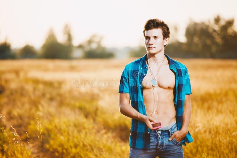 Przystojny młody Kaukaski facet z mięśniowym ciałem słucha muzyka na głowie ubierał w błękit rozpinającej koszula i drelichów skr obrazy stock