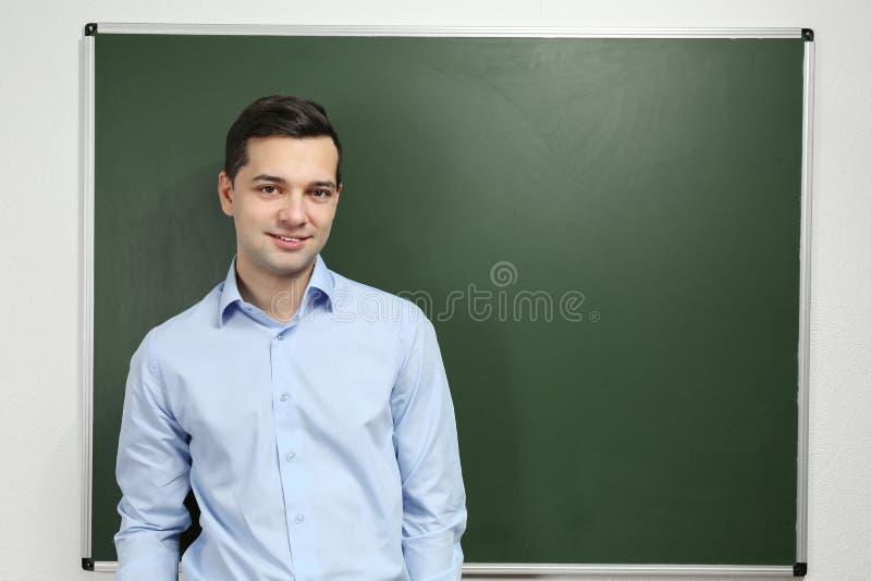 Przystojny młody nauczyciel blisko blackboard zdjęcie royalty free