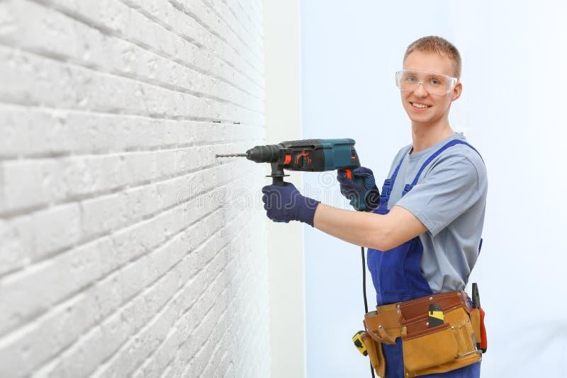 Przystojny młody pracujący mężczyzna używa obrotowego młot Domowa naprawa fotografia royalty free