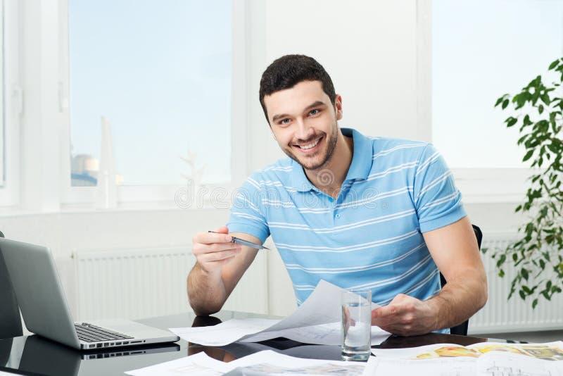 Przystojny młody projektant wnętrz przy miejscem pracy zdjęcie stock