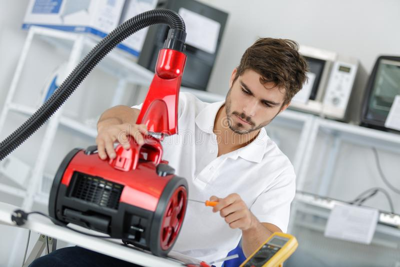 Przystojny młody repairman załatwia próżniowego cleaner zdjęcia stock