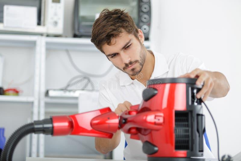 Przystojny młody repairman załatwia próżniowego cleaner fotografia royalty free