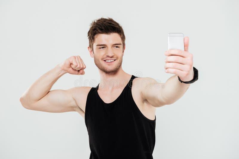 Przystojny młody sportowiec z telefonem robi selfie zdjęcia stock