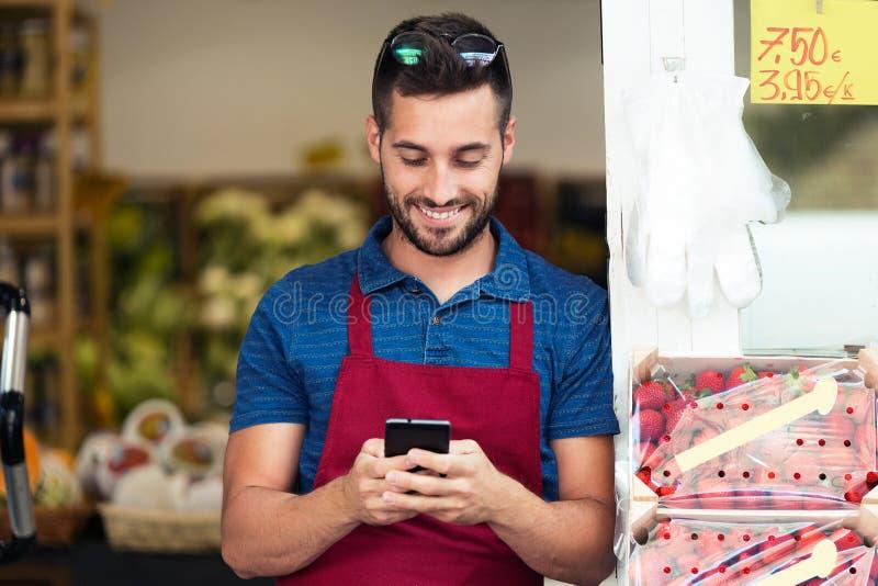 Przystojny młody sprzedawca używa jego telefon komórkowego w zdrowie sklepu spożywczego sklepie obraz stock