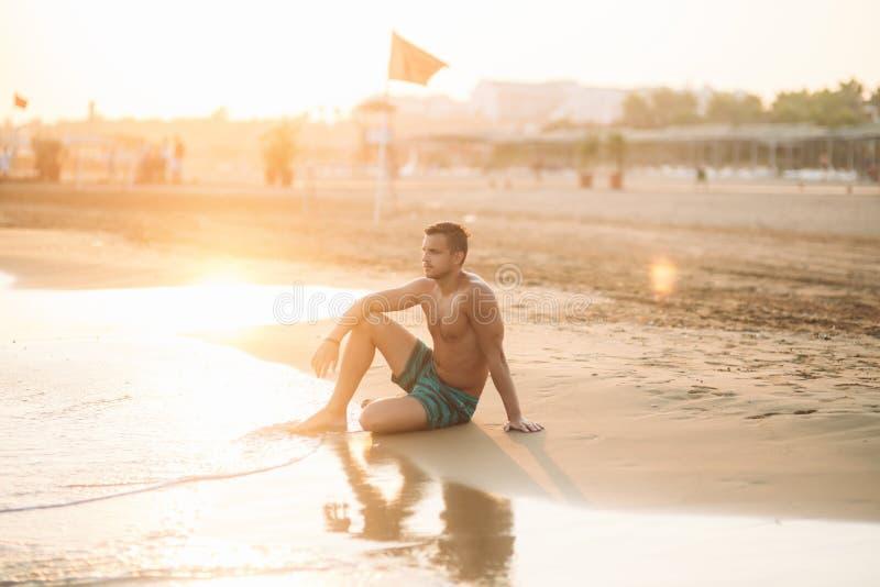Przystojny m??czyzna na piaskowatej pla?y siedzi na seashore M?ody cz?owiek na wybrze?u fotografia royalty free
