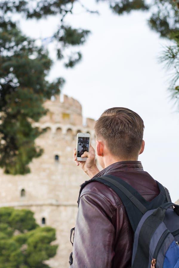 Przystojny m??czyzna, turysta, z plecakiem bierze obrazkom na smartphone Bia?y wierza w centrum Saloniki, Grecja fotografia royalty free