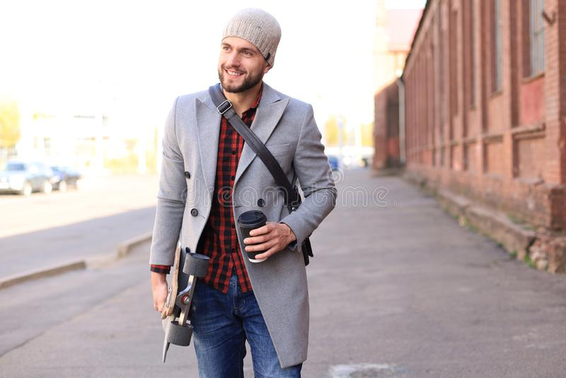 Przystojny m?ody cz?owiek w popielatym ?akieta i kapeluszu odprowadzeniu na ulicznym, u?ywa? longboard fotografia royalty free