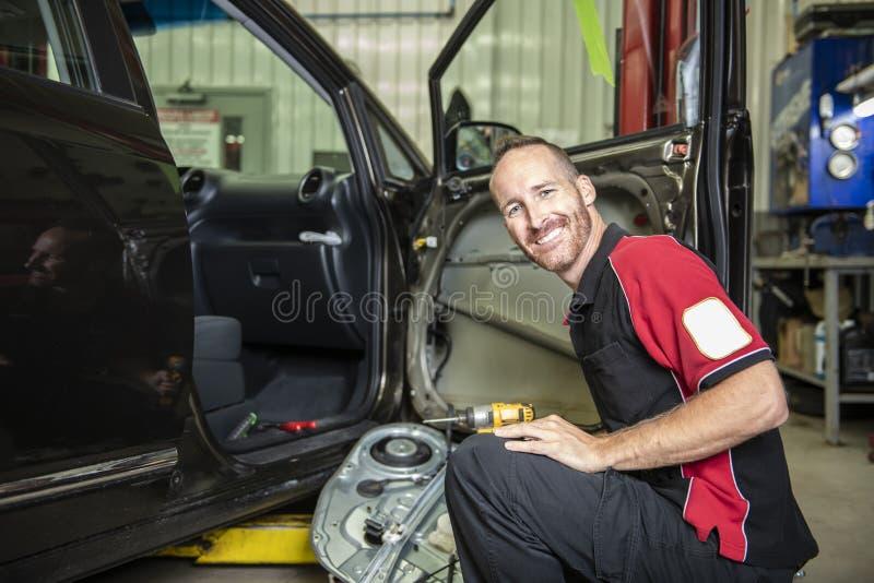 Przystojny mechanik opierający się na samochodzie w auto remontowym sklepie obrazy royalty free