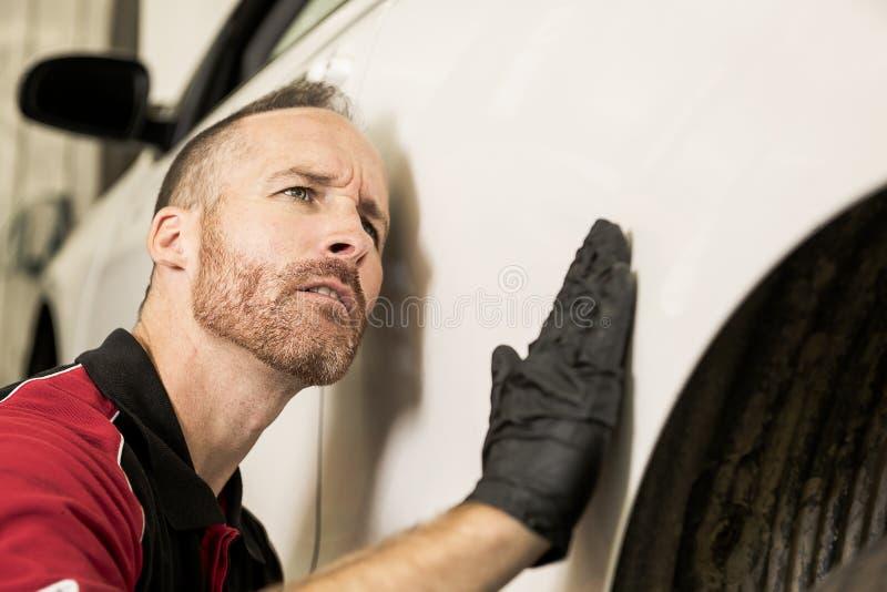 Przystojny mechanik opierający się na samochodzie w auto remontowym sklepie zdjęcia stock