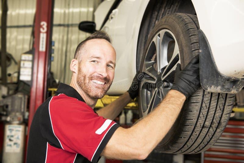 Przystojny mechanik opierający się na samochodzie w auto remontowym sklepie fotografia royalty free
