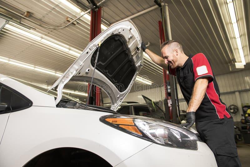 Przystojny mechanik opierający się na samochodzie w auto remontowym sklepie zdjęcie royalty free