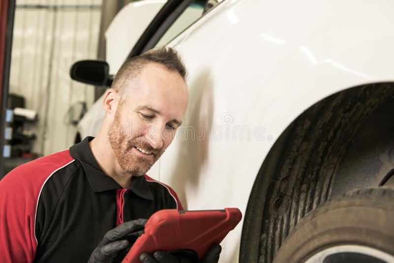 Przystojny mechanik opierający się na samochodzie w auto remontowym sklepie z pastylką na ręce fotografia stock