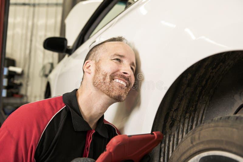 Przystojny mechanik opierający się na samochodzie w auto remontowym sklepie z pastylką na ręce obrazy royalty free