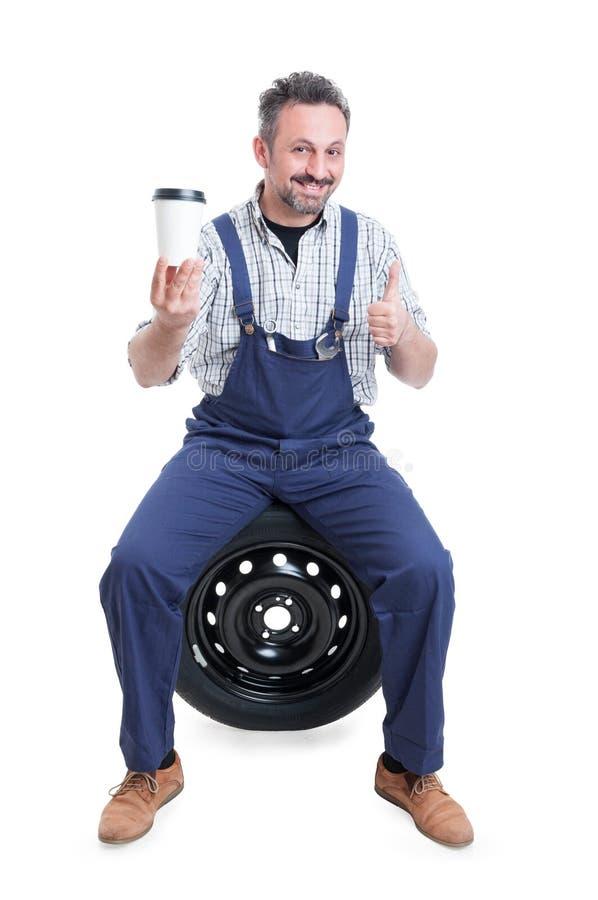 Przystojny mechanik robi jak gest i pije kawę zdjęcie royalty free