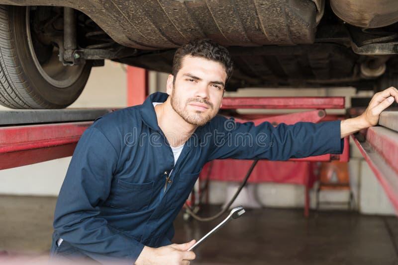 Przystojny mechanika mienia Spanner Pod samochodem fotografia royalty free