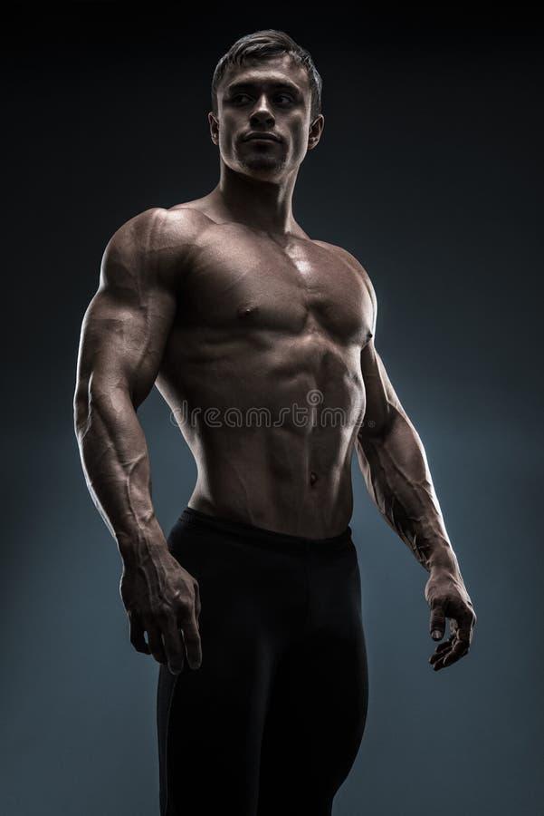 Przystojny mięśniowy bodybuilder pozuje nad czarnym tłem obraz royalty free