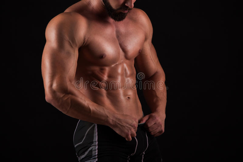 Przystojny mięśniowy bodybuilder pozuje nad czarnym tłem zdjęcie stock
