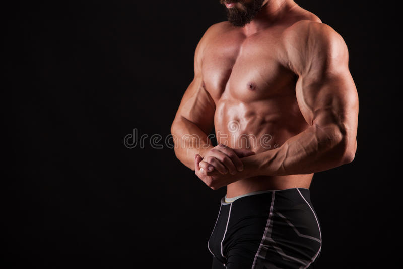 Przystojny mięśniowy bodybuilder pozuje nad czarnym tłem obrazy stock