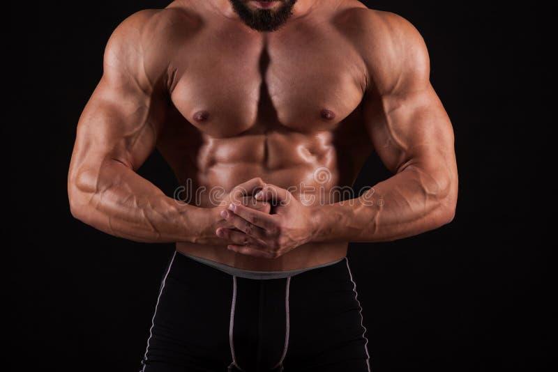 Przystojny mięśniowy bodybuilder pozuje nad czarnym tłem obraz stock