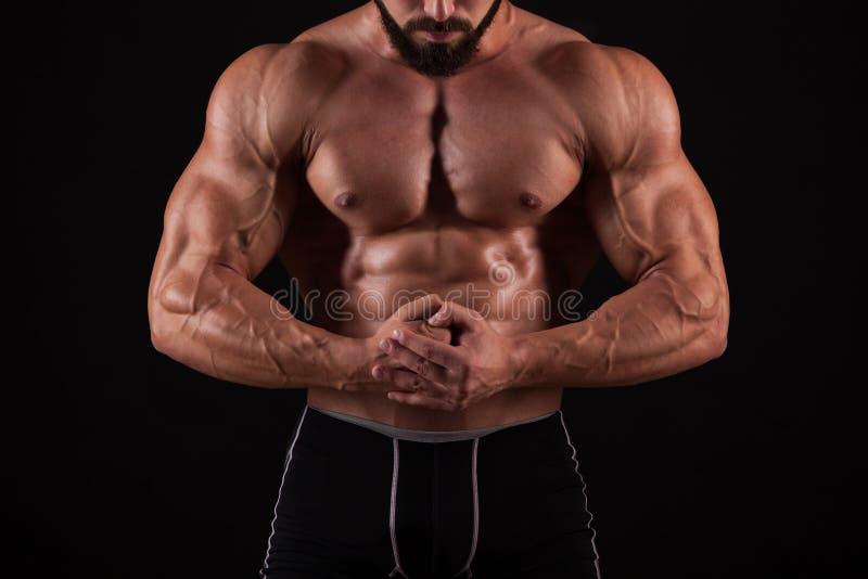 Przystojny mięśniowy bodybuilder pozuje nad czarnym tłem zdjęcia stock