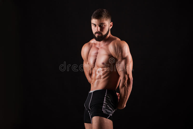 Przystojny mięśniowy bodybuilder pozuje nad czarnym tłem zdjęcie royalty free